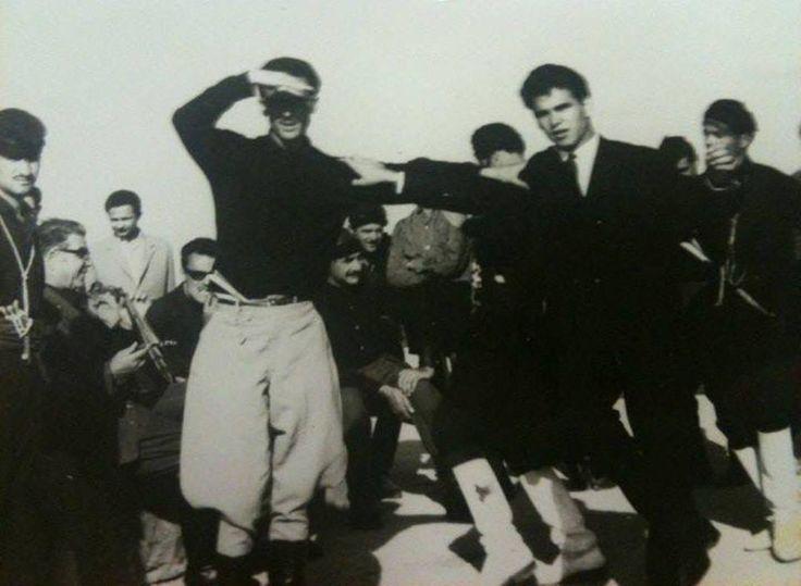 """""""Στον ουρανό χορεύγουνε, στον Άδη κάνουν γάμο"""": Μια συλλεκτική φωτογραφία από το 1964. O Nίκος Ξυλούρης χορεύει με τον Βασίλη Σκουλά, υπό τους ήχους της λύρας του Δερμιτζογιάννη"""
