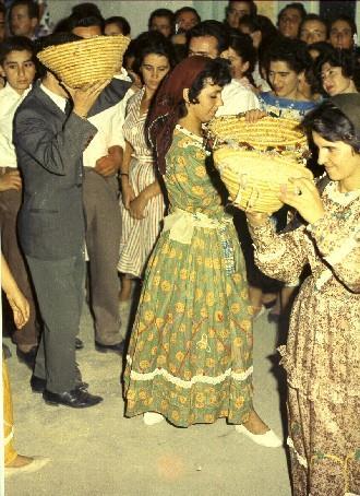 Κοπέλες φορώντας της κυπριακή παραδοσιακή στολή χορεύουν κρατώντας ψάθινα καλάθια με σιτάρι, κατά το γλέντι παραδοσιακού γάμου στην Πάφο το 1954. ΛΕΒΕΝΤΕΙΟ ΜΟΥΣΕΙΟ