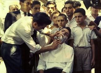 Έγρωμη φωτογραφία του 1954. Ο κουμπάρος ξυρίζει το γαμπρό παρουσία συγγενών και πολλών παιδιών. ΛΕΒΕΝΤΕΙΟ ΜΟΥΣΕΙΟ